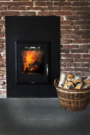 woodburning: Fireplace in a brick wall and woods in basket Stock Photo