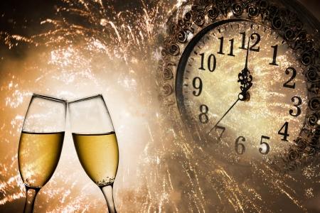 brindisi champagne: Capodanno s a mezzanotte con bicchieri di champagne e orologio su sfondo chiaro