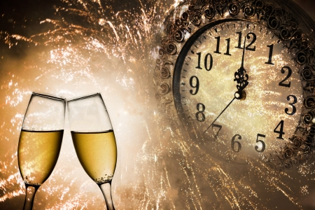 Champagne glasses, clock and fireworks at midnight photo