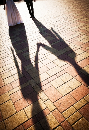 Funny shadows of a couple hand in hand walking in a pavement square in the dusk lighting photo