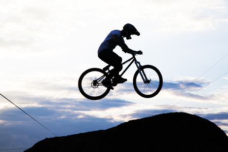 bmx bike: Silhouette of a man doing a jump with a bmx bike