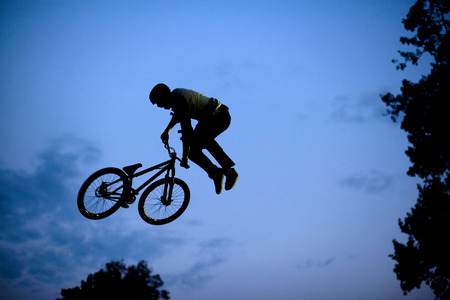 bmx bike: Silhouette of a man doing a jump with a bmx bike
