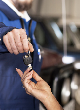 giving back: Handsome car mecanic giving back the keys to the client Stock Photo