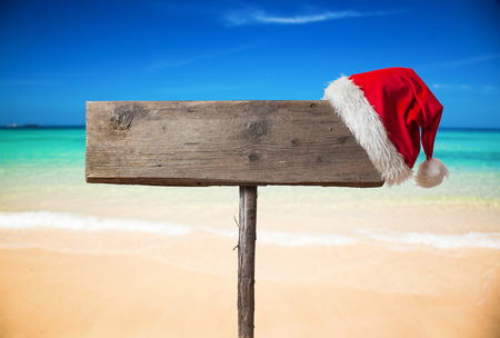 Wooden signboard with Christmas hat on tropical beach photo