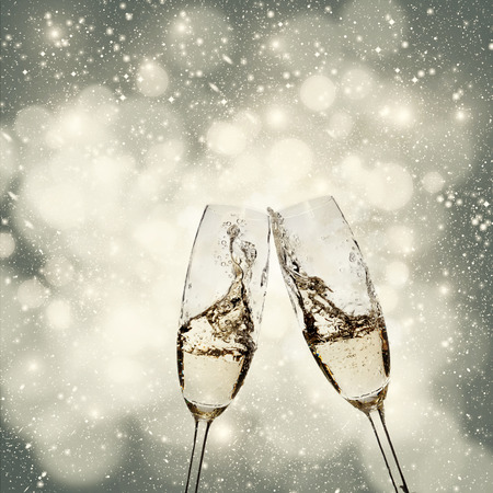 Toasting with champagne glasses on sparkling holiday background photo