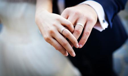Mãos e anéis no buquê de casamento