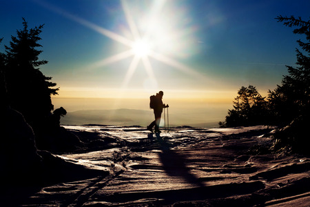 arri�re-pays: Backcountry skier reaching the summit at sunset