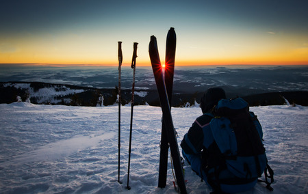 Backcountry skier reaching the summit at sunset photo