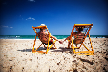 Couple sitting in beach chairs and holding hands on a tropical beach