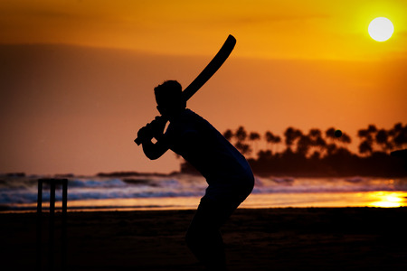 Boy spelen cricket bij zonsondergang op tropisch strand in Sri Lanka