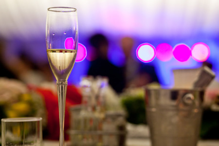 champagne glass: Glass with champagne lit by nightclub lights Stock Photo