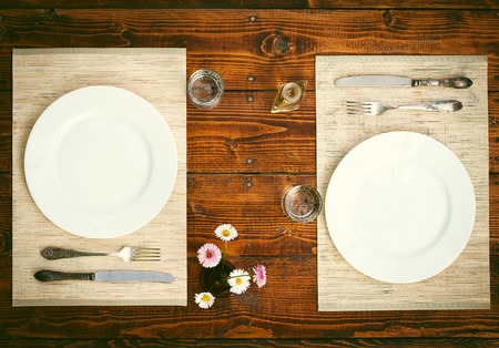 romantic places: Table setting for two with empty plates - rustic wooden table Stock Photo