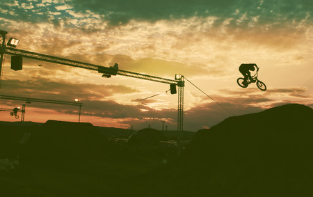 bmx bike: Silhouette of a man doing a jump with a bmx bike against sunset sky