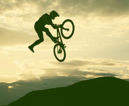 bmx bike: Silhouette of a man doing a jump with a bmx bike against sunset sky