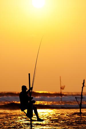 fishman: Silhouettes of the traditional stilt fishermen at sunset near Galle in Sri Lanka Stock Photo