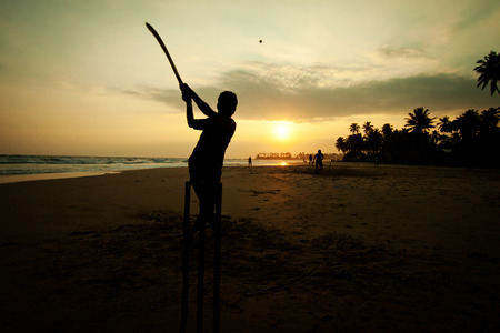 sri: Boy playing cricket at sunset on tropical beach in Sri Lanka