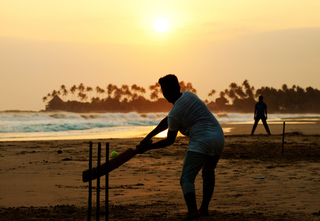 cricket: Boy playing cricket at sunset on tropical beach in Sri Lanka