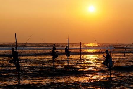 galle: Silhouettes of the traditional stilt fishermen at sunset near Galle in Sri Lanka Stock Photo