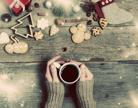 wine background: Christmas decorations, home made ginger bread and womans hand on mulled wine on rustic wooden background