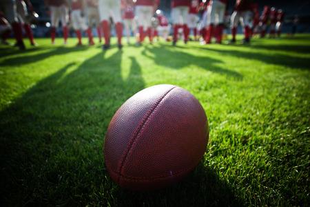 Primo piano di un football americano sul campo, i giocatori in background Archivio Fotografico - 46934094