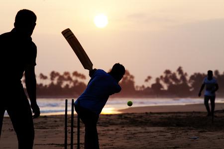 balones deportivos: Muchacho que juega al grillo en la puesta de sol en la playa tropical en Sri Lanka Foto de archivo
