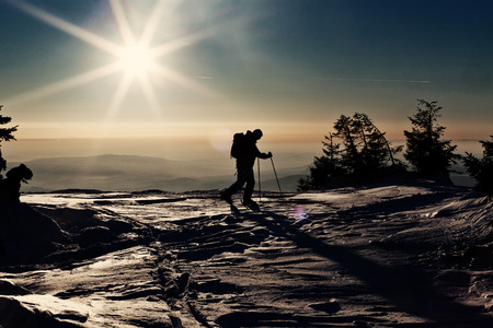 backcountry: Backcountry skier reaching the summit at sunset