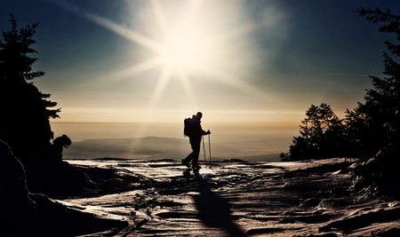 guide: Backcountry skier reaching the summit at sunset