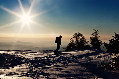 offpiste: Backcountry skier reaching the summit at sunset