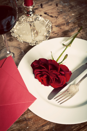 romantic couple: Table setting with red roses on plate - celebrating Valentines Stock Photo