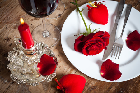 china rose: Table setting with red roses on plate - celebrating Valentines Stock Photo