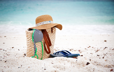 Straw hat and bag on a tropical beach Stock Photo