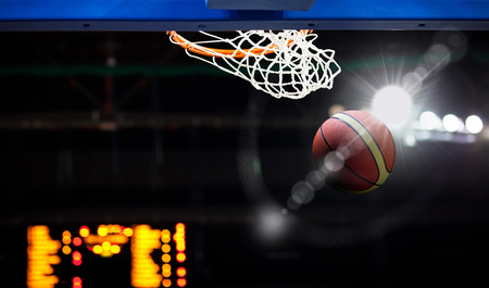 nba: Basketball going through the hoop at a sports arena