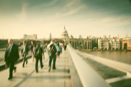 ondon: Blurred background of crowd of people on millennium bridge and st pauls cathedral in background, london
