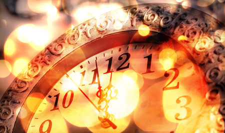 12 month old: old clock with fireworks and holiday lights - New Years at midnight Stock Photo