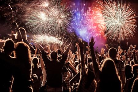 新年の休日の祭典の背景に花火を見て歓声を上げる群衆