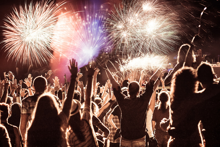 cheering crowd watching fireworks at New Year - holiday celebration background Standard-Bild