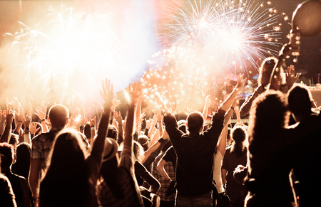 party friends: cheering crowd watching fireworks at New Year - holiday celebration background Stock Photo