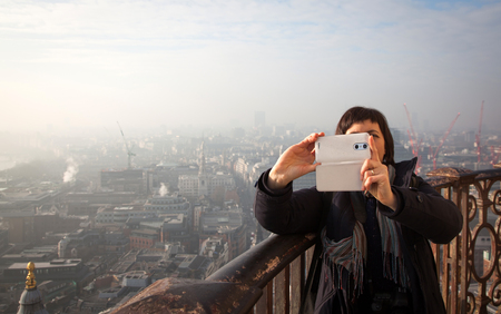 st pauls: woman taking a selfie from the rooftop of St Pauls Cathedral on a foggy day in London, UK - city break - tourism concept