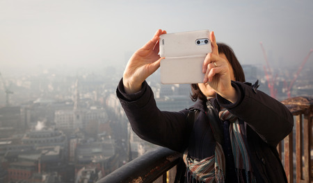 woman taking a selfie from the rooftop of St Paul's Cathedral on a foggy day in London, UK - city break - tourism concept photo