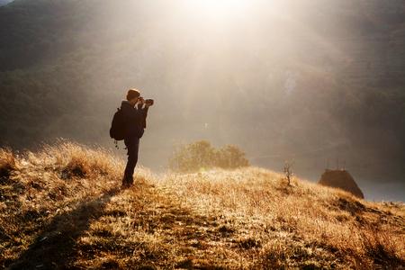 female photographer at sunrise, misty mountains, Romania