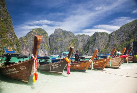 KO PHI PHI, THAILAND, February 1, 2014: Traditional long tail boats on the beach of Maya Bay, Ko Phi Phi Leh, Andaman Sea, famous tourist destination in the Ko Phi Phi achipelago