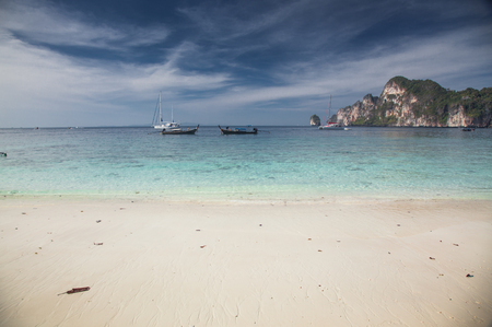 KO PHI PHI, THAILAND, February 1, 2014: Tropical beach with traditional long tail boats on the beach of Ko Phi Phi, Andaman Sea, famous tourist destination in Thailand Publikacyjne