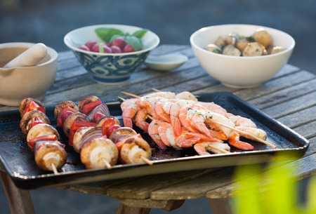 barbecue in the garden - summer- prawns and vegetables on skewers