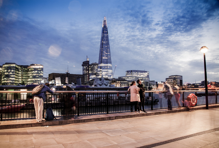 LONDON, UK - JULY 17, 2017: tourists on the South bank watching London skyline with the Shard at night