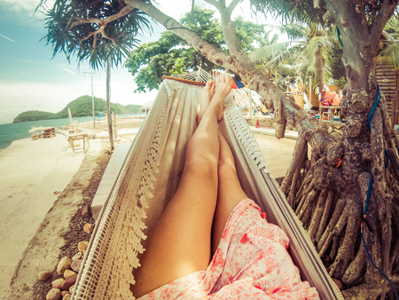 legs of woman relaxing in hammock on a tropical beach