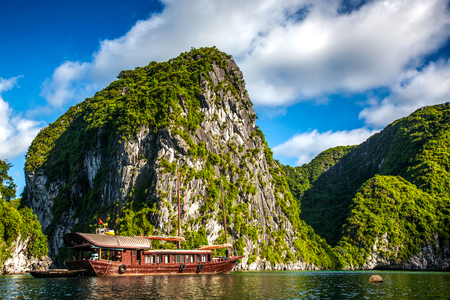 cruising among beautiful limestone rocks and secluded beaches in Ha Long bay, Vietnam. Reklamní fotografie - 85322837