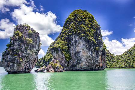 cruising among beautiful limestone rocks and secluded beaches in Ha Long bay, Vietnam.