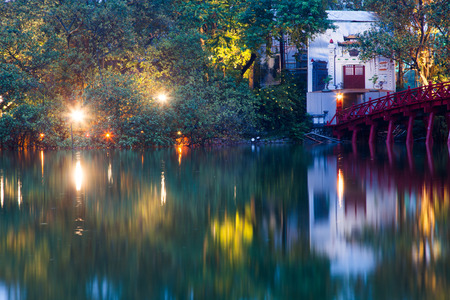 hanoi Red Bridge at night. The wooden red-painted bridge over the Hoan Kiem Lake connects the shore and the Jade Island on which Ngoc Son Temple stands. Stock Photo