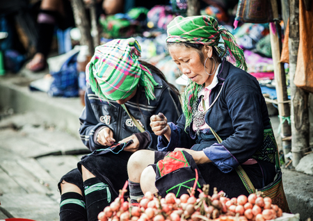 SA PA, VIETNAM - AUGUST 2017: Portrait of black hmong ethnic minority woman selling goods and sewing at the market in Sa Pa town, the high mountains, Lao Cai province, Vietnam