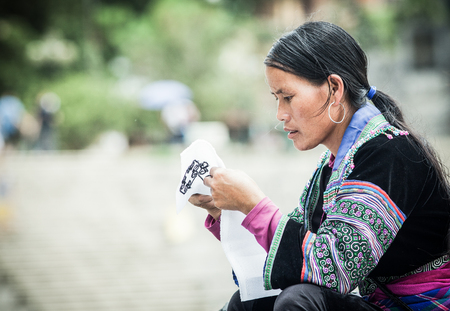 SA PA, VIETNAM - AUGUST 2017: Portrait of unidentified hmong woman sewing in Sa Pa town, the high mountains, Lao Cai province, Vietnam.